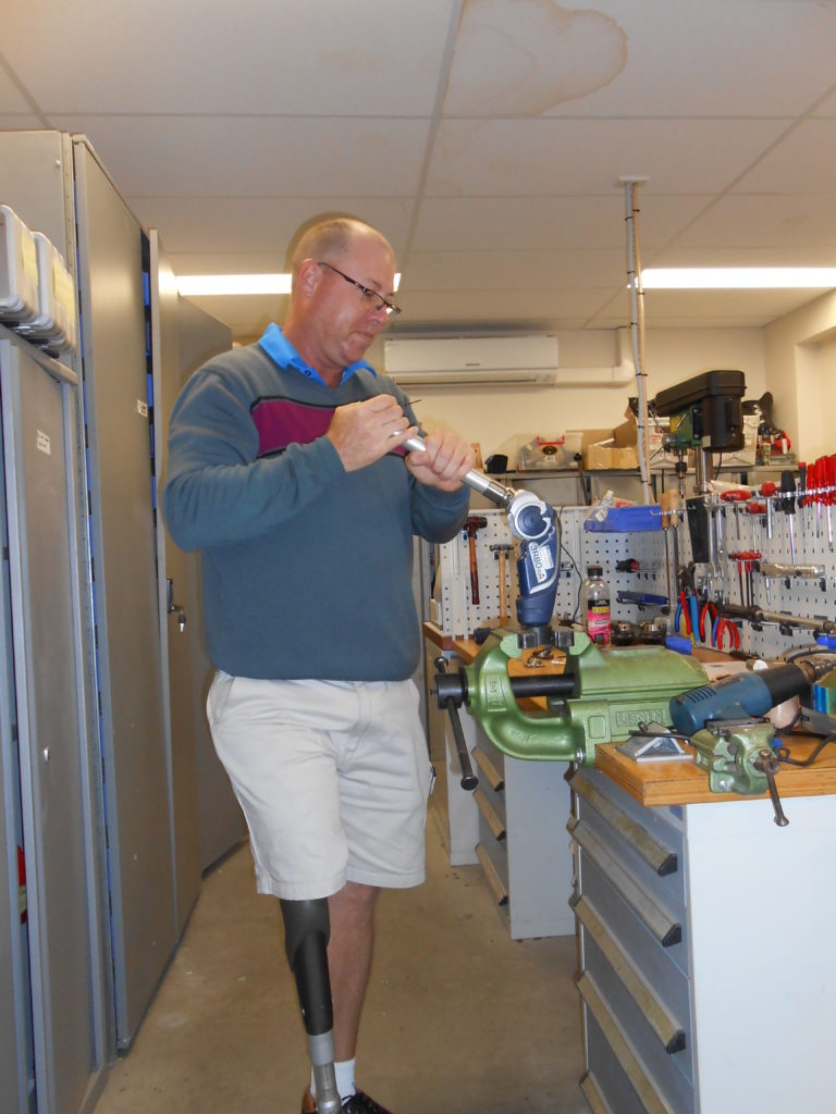 Steve, aged 56, in his workshop. His prosthetic leg is visible under his shorts.