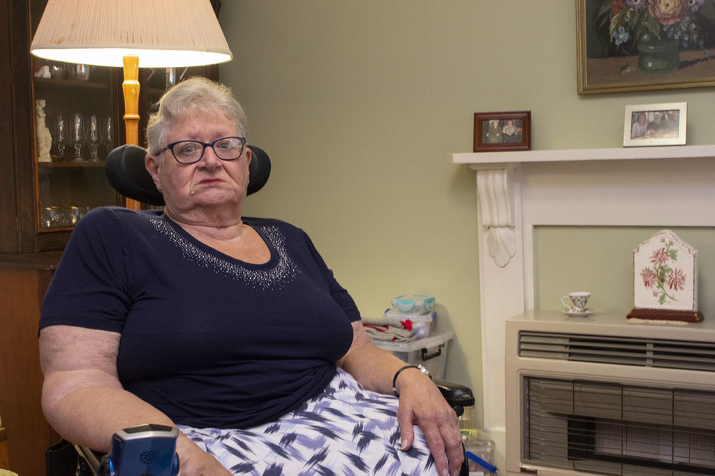 Lyn Bates, 74, sits in her motorised wheelchair in her living room.