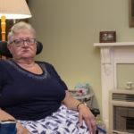 Lyn Bates, 74, sits in her motorised wheelchair in her living room.