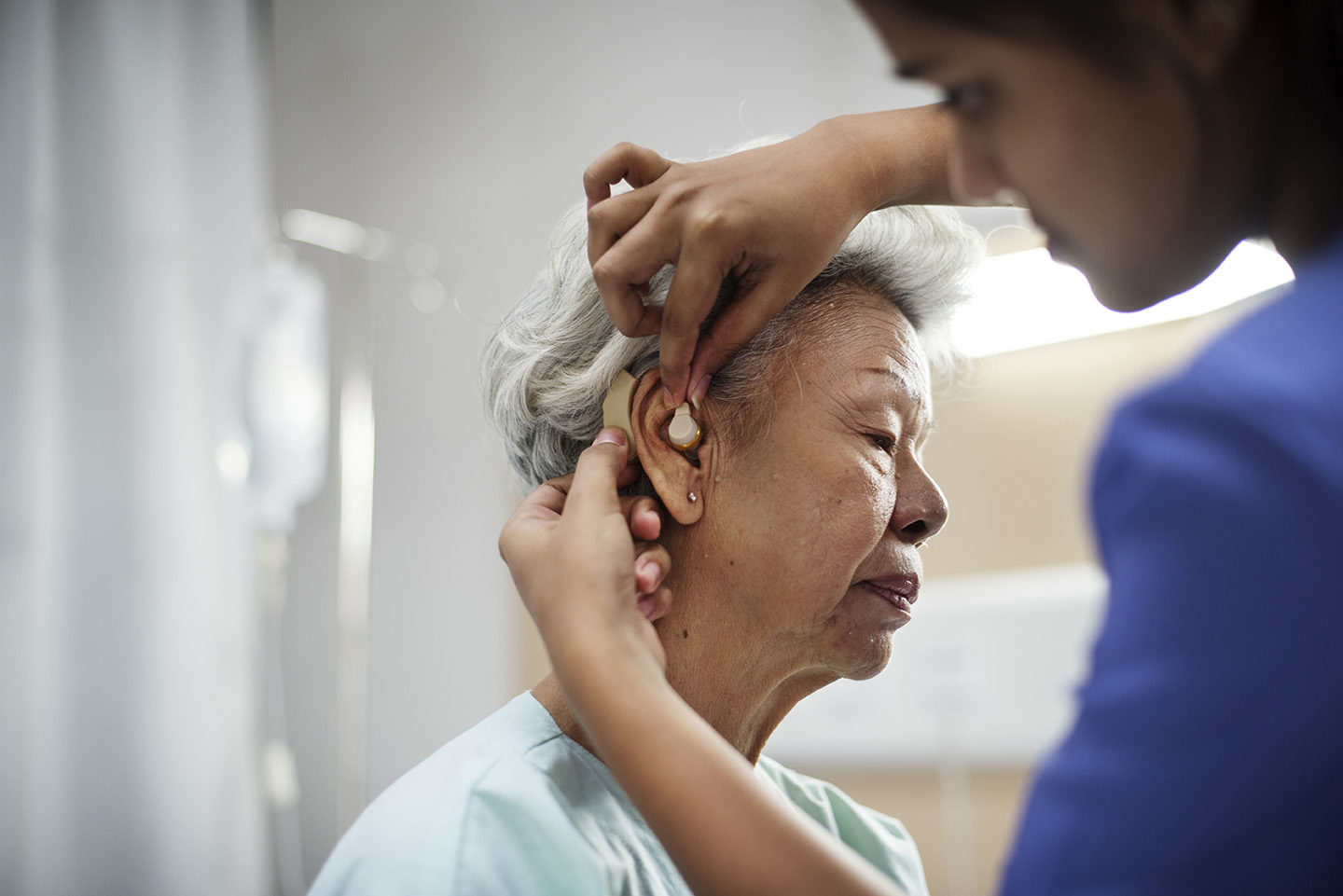 An older woman is fitted with a hearing aid.