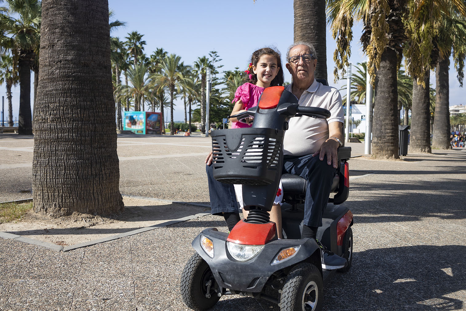 An older man sits on his mobility scooter with his granddaughter. They're on a footpath lined with palm trees.