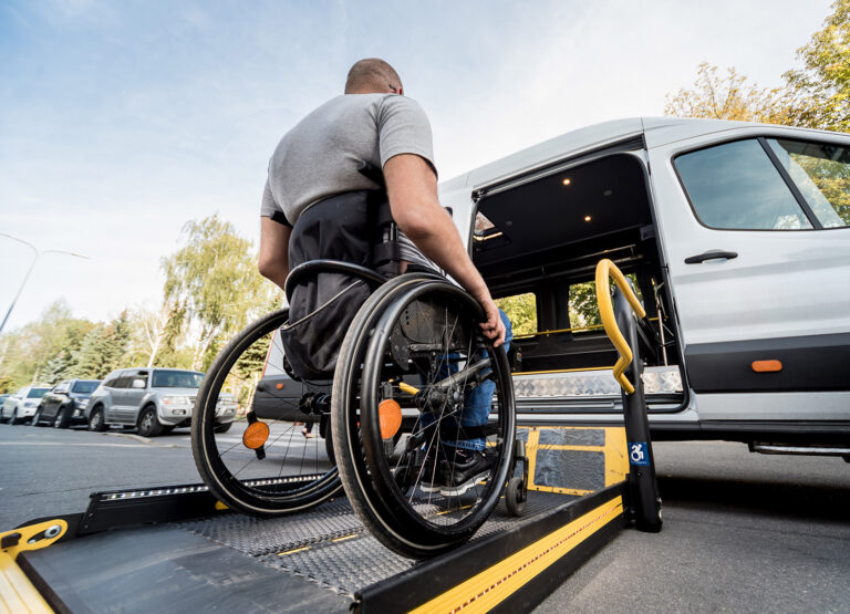 A man in a wheelchair uses a lift to access an accessible vehicle.