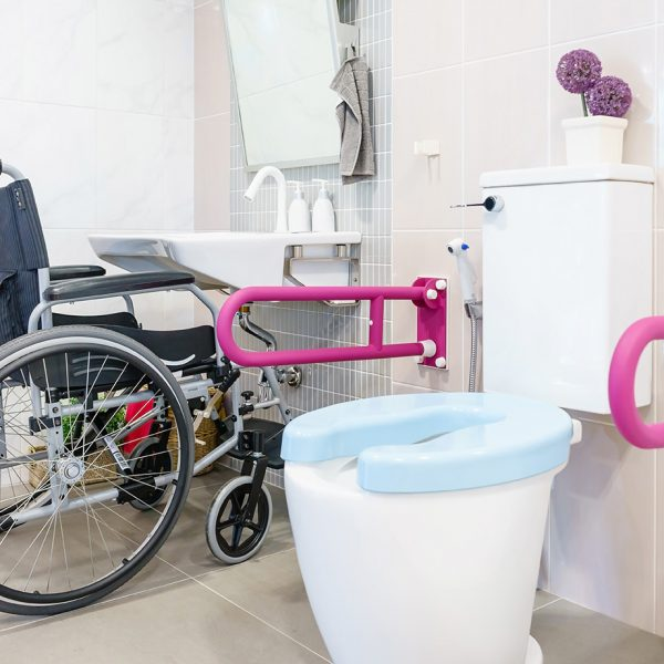 An accessible bathroom in someone's home. It shows a handrail on either side of the toilet and a raised hand-basin allowing a wheelchair to pull up to use it.