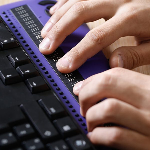 A pair of hands using computer with braille computer display and a computer keyboard.
