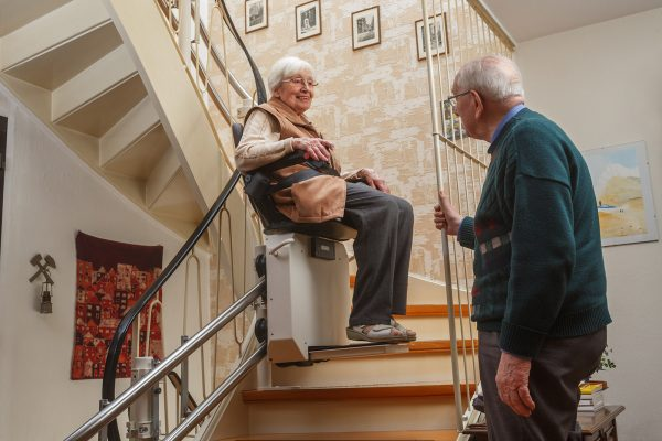 An older woman sits on a chair lift going up stairs in her house, with her husband watching.
