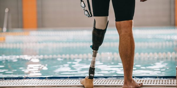 A cropped photo of a swimmer's legs at the poolside. His left leg is a prosthetic.